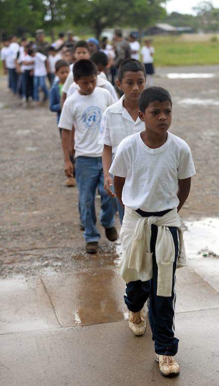 Children from the surrounding communities arrive at Puerto Castillo Naval Base in Trujillo, Honduras, June 6, 2015, to participate in the Guardians of the Fatherland event. Guardians goes twice and year and includes about 200 children per session. Each session lasts about 6 months, every Saturday and includes classes on civic values, military values, spiritual values and human rights. More than 20 NEW HORIZONS Honduras 2015 personnel volunteered to participate in the event. NEW HORIZONS was launched in the 1980s and is an annual joint humanitarian assistance exercise that U.S. Southern Command conducts with a partner nation in Central America, South America or the Caribbean. The exercise improves joint training readiness of U.S. and partner nation civil engineers, medical professionals and support personnel through humanitarian assistance activities. (U.S. Air Force photo by Capt. David J. Murphy/Released)