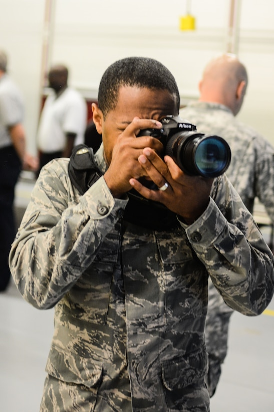 U.S. Air Force Senior Airman Bruce Jenkins, a crew chief assigned to the 139th Maintenance Group, Missouri Air National Guard, photographs an event at Rosecrans Air National Guard Base, St. Joseph, Mo., June 3, 2015. Jenkins is a temporary technician assigned to the 139th Public Affairs Office as an audiovisual production specialist. (U.S. Air National Guard photo by Tech. Sgt. Michael Crane)