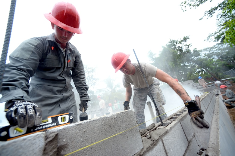 Painesville, Ohio, native U.S. Air Force Staff Sgt. Nathan Rosier, 823rd Expeditionary RED HORSE Squadron structural supervisor, out of Hurlburt Field, Fla., works with U.S. Air Force Senior Airman Jason Berry, 823rd ERHS water and fuels systems maintenance journeyman, and Grand Rapids, Mich. native, to lay brick during the construction of a new school building at the Gabriela Mistral primary school in Ocotes Alto, Honduras, June 3, 2015. Berry describes the relationship of the two brick layers as one of a doctor and nurse, as he places the mortar while Rosier lays the bricks. The construction project is one part of the New Horizons Honduras 2015, an annual humanitarian and training exercise put on by U.S. Southern Command. New Horizons was launched in the 1980s and is an annual joint humanitarian assistance exercise that U.S. Southern Command conducts with a partner nation in Central America, South America or the Caribbean. The exercise improves joint training readiness of U.S. and partner nation civil engineers, medical professionals and support personnel through humanitarian assistance activities. (U.S. Air Force photo by Capt. David J. Murphy/Released)