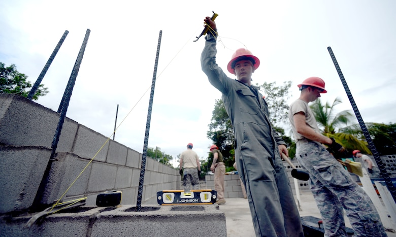 U.S. Air Force Staff Sgt. Nathan Rosier, 823rd Expeditionary RED HORSE Squadron structural supervisor, out of Hurlburt Field, Fla., uses a string to set atraight path for bricks during the construction of a new school building at the Gabriela Mistral primary school in Ocotes Alto, Honduras, June 3, 2015. Rosier, a Painesville, Ohio native, is working a project which is one part of the New Horizons Honduras 2015, an annual humanitarian and training exercise put on by U.S. Southern Command. New Horizons was launched in the 1980s and is an annual joint humanitarian assistance exercise that U.S. Southern Command conducts with a partner nation in Central America, South America or the Caribbean. The exercise improves joint training readiness of U.S. and partner nation civil engineers, medical professionals and support personnel through humanitarian assistance activities. (U.S. Air Force photo by Capt. David J. Murphy/Released)