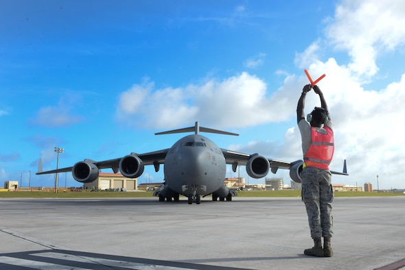 Airman 1st Class David Reed, 734th Air Mobility Squadron crew chief, marshals a C-17 Globemaster III,  April 18, 2015, on the flightline at Andersen Air Force Base, Guam. Airmen from the 36th Wing and the 734th AMS work to project global reach and allow military leaders to employ airpower across the entire spectrum of engagement. (U.S. Air Force photo by Senior Airman Katrina M. Brisbin/Released)