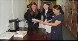 US Army Corps of Engineers Far East District operations officer Maj. L. Dot Browning greeting participants and handing out workshop materials during a water resource management strategy workshop in Ulaanbaatar, Mongolia.