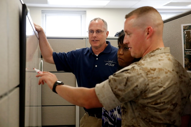 Francis Bonner (left) talks to members of his team about modifications to the Common Aviation Command and Control System, or CAC2S, in his office on Marine Corps Base Quantico, Virginia. Bonner will receive the 2014 Assistant Secretary of the Navy for Research, Development and Acquisition Dr. Delores M. Etter Top Scientists and Engineers Award for his achievements as lead engineer for the CAC2S program at Program Executive Officer Land Systems.