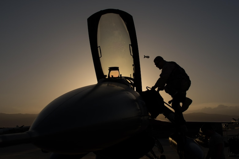 U.S. Air Force Capt. Doug Mayo, 555th Expeditionary Fighter Squadron, enters an F-16 Fighting Falcon aircraft before conducting a preflight inspection with Staff Sgt. William Harris, 455th Expeditionary Maintenance Squadron crew chief, at Bagram Airfield, Afghanistan, June 8, 2015. The 455th EAMXS ensure Fighting Falcons on Bagram are prepared for flight and return them to a mission-ready state once they land.  (U.S. Air Force photo by Tech. Sgt. Joseph Swafford/Released)