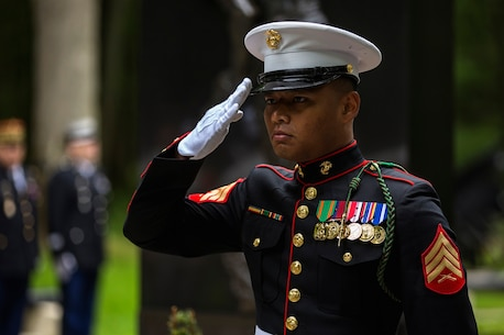 U.S. Marine Corps Sgt. Noukane Sonethanouvong, radio operator with communications company, headquarters battalion, 1st Marine Division  salutes while taps is played during a private ceremony at Aisne-Marne American Cemetery in Belleau, France on May 31, 2015. This Memorial Day ceremony was held in honor of the 97th anniversary of the Battle of Belleau Wood. (U.S. Marine Corps photo by Lance Cpl. Akeel Austin/Released)