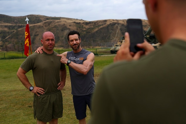Sergeant Jeran Black, a squad leader assigned to India Co., 3rd Battalion, 5th Marine Regiment, poses for a photo with the creator of P90X, Tony Horton aboard Camp Pendleton, Calif., June 9, 2015. Horton visited the Marines and spent the morning conducting physical training and answering questions the Marines had.