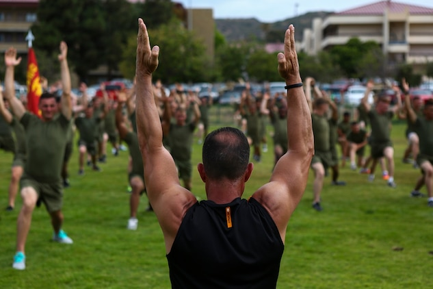 Juan Urquiaga, a trainer with Tony Horton, the creator of the fitness program P90X, demonstrates an exercise for Marines assigned to 3rd Battalion, 5th Marine Regiment, aboard Camp Pendleton, Calif., June 9, 2015. Horton believes Marines need to focus on nutrition and a wide variety of exercises to be ready for any mission as may be directed.