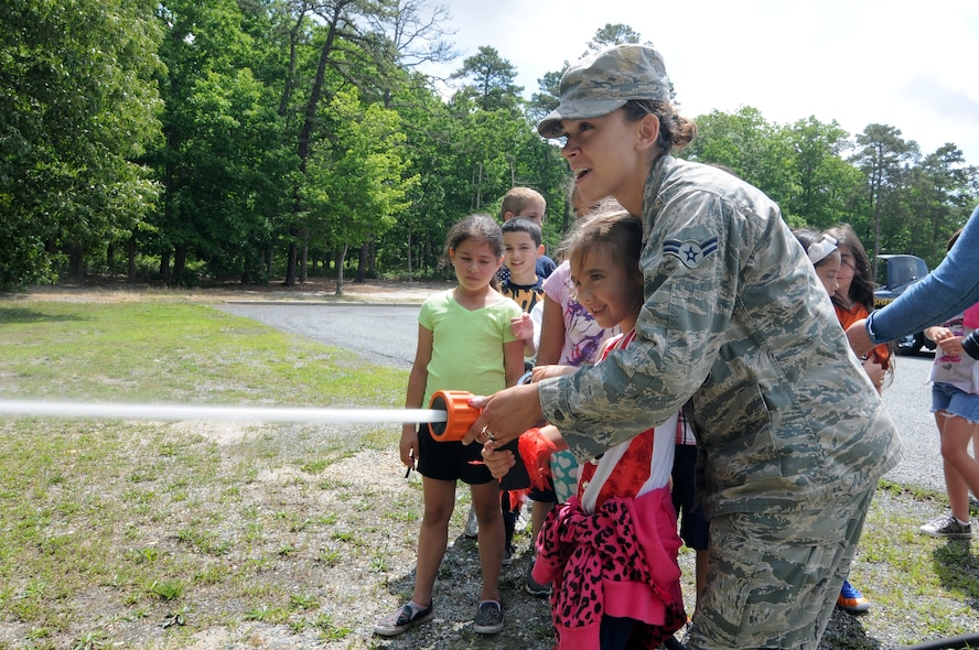 U.S. Air Force Airman 1st Class Brooke Hunt, from the New Jersey Air National Guard's 177th Fighter Wing Fire Department, helps a student use a fire hose on June 9, 2015 at Alder Avenue Middle School's Not All Heroes Wear Capes event in Egg Harbor Township, N.J. Local first responders and military personnel gathered at the school to provide a hands-on educational experience for students, teaching them about the services they provide to the local community. (U.S. Air National Guard photo by Airman 1st Class Amber Powell/Released)