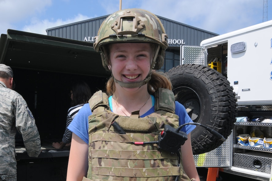 A student from Alder Avenue Middle School in Egg Harbor Township, New Jersey, wears a tactical vest and ballistic helmet before checking out the inside of a humvee from the New Jersey Air National Guard's 177th Fighter Wing on June 9, 2015. The school's Not All Heroes Wear Capes event provided local first responders and military personnel with the opportunity to provide a hands-on educational experience for students, showing what their services provide the local community. (U.S. Air National Guard photo by Airman 1st Class Amber Powell/Released)
