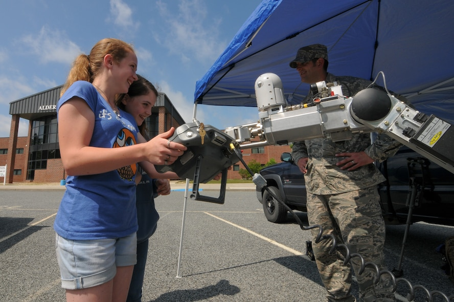 U.S. Air Force Tech. Sgt. Philip Douglass, 177th Civil Engineer Squadron explosive ordnance disposal technician, explains the basic operation of an Air Force Medium-Sized Robot to students from Alder Avenue Middle School in Egg Harbor Township, New Jersey on June 9, 2015. Members of the New Jersey Air National Guard and local first responders brought out equipment and set up displays to teach students about the services they provide to the community. (U.S. Air National Guard photo by Airman 1st Class Amber Powell/Released)