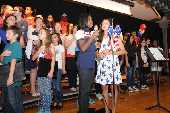 A picture of students singing the national anthem.