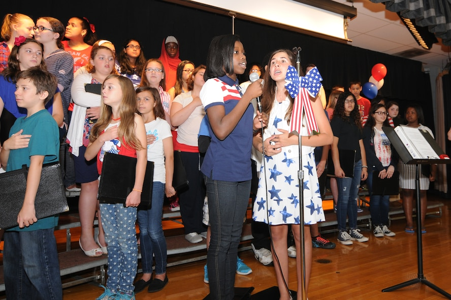 Students from Alder Avenue Middle School in Egg Harbor Township, New Jersey, sing the national anthem to kick off the school's Not All Heroes Wear Capes event on June 9, 2015. Local first responders and military personnel gathered at the school to be honored and to provide a hands-on educational experience for students. (U.S. Air National Guard photo by Airman 1st Class Amber Powell/Released)
