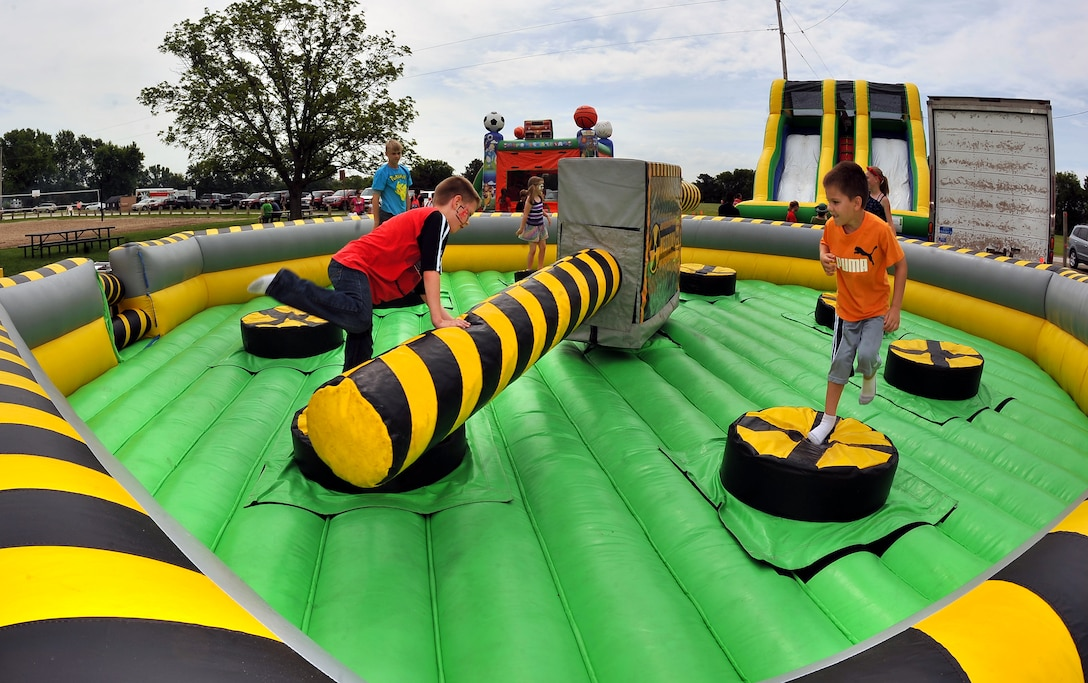 Kids jump and duck under the rotating arms of one of several inflatable activities spread throughout the Offutt Appreciation Day Picnic.  The picnic has been hosted by the Offutt Advisory Council for more than twenty years.  (U.S. Air Force photo by Josh Plueger)