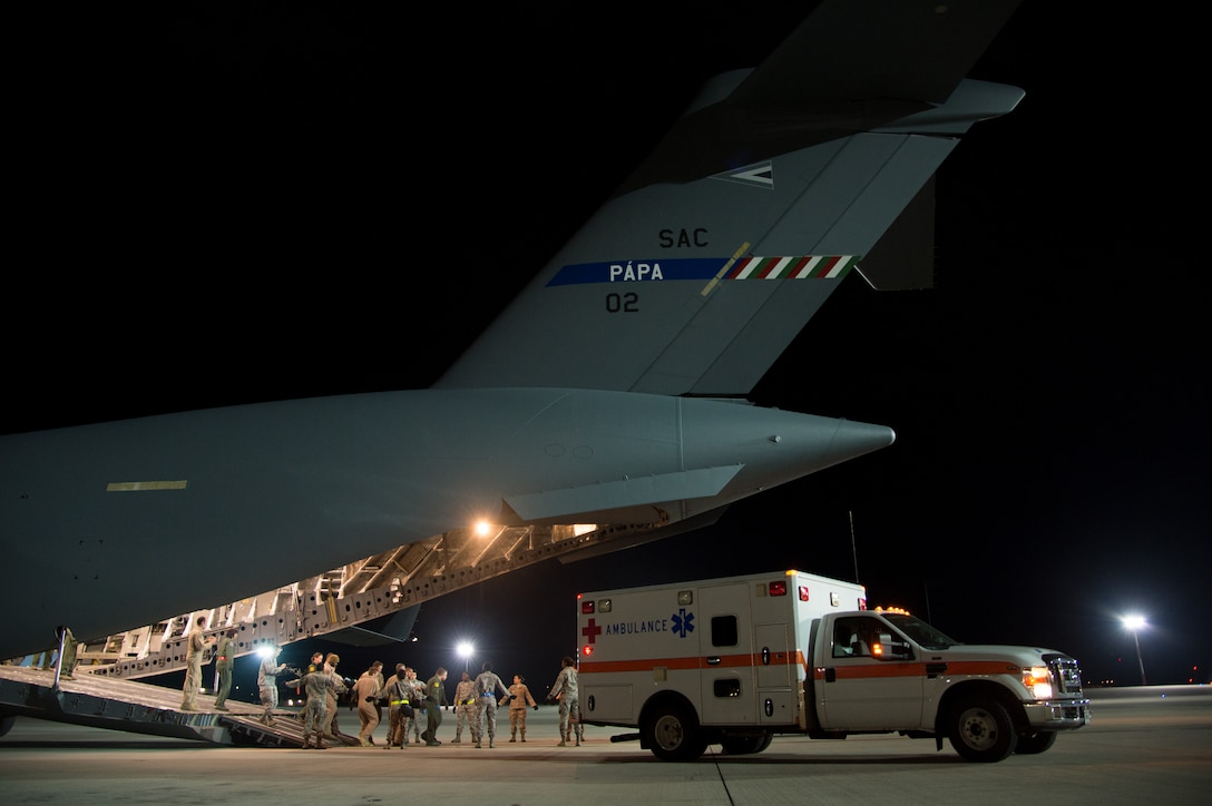 Patients are transferred into an ambulance where they will be transported to receive further medical care June 8, 2015, at Ramstein Air Base, Germany. Ramstein Airmen looked after the patients as they were being transported by military members from Strategic Airlift Capability Heavy Airlift Wing based at   Pápa Air Base, Hungary. This was the first time both bases joined together for a critical care aeromedical transport. (U.S. Air Force photo/Senior Airman Jonathan Stefanko)