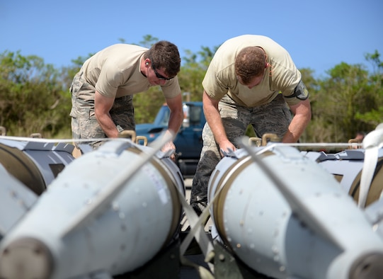 Staff Sgt. Nicholas Eder, 36th Munitions Squadron line delivery driver, and Tech. Sgt. Tyler Harrill, 7th Munitions Squadron munitions storage supervisor, tie down guided bomb units prior to delivering them to a weapons in-check station, June 1, 2015, Andersen Air Force Base, Guam. The 2015 Combat Ammunition Production Exercise included more than 250 Airmen from nine bases across the Pacific and U.S. (U.S. Air Force photo by Airman 1st Class Joshua Smoot/Released)