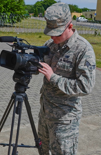 Senior Airman Steven Adkins, a broadcast journalist assigned to American Forces Network, Spangdahlem Air Base, Germany, focuses his video camera during an assignment for Saber Strike 15 on June 7, 2015, in the Drawsko Pomorskie Training Area in Poland. Saber Strike is a long-standing U.S. Army Europe-led cooperative training exercise. This year's exercise objectives facilitate cooperation amongst the U.S., Estonia, Latvia, Lithuania, and Poland to improve joint operational capability in a range of missions as well as preparing the participating nations and units to support multinational contingency operations. (U.S. Army photo by Sgt. Brandon Anderson, 13th Public Affairs Detachment/Released.)