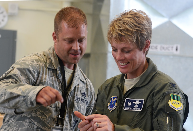 Master Sgt. William Huff, 2nd Maintenance Squadron deployed from Barksdale Air Force Base to the 36th Munitions Squadron, presents a coin to Col. Kristin Goodwin, 2nd Bomb Wing commander, June 3, 2015, at Andersen Air Force Base, Guam. Goodwin toured Andersen to meet with the units and Airmen in support of U.S. Pacific Command's Continuous Bomber Presence mission. (U.S. Air Force photo by Airman 1st Class Arielle Vasquez/Released)