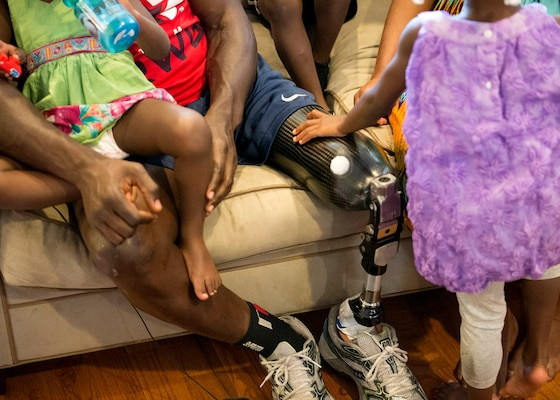 Gabrielle Reynolds, 4, touches her dad, retired Army Capt. Will Reynolds' prosthetic leg as the family settles in for the evening, May 27, 2015. Reynolds said the children like to assist him with his running and walking legs. He is competing in the Department of Defense Warrior Games in June. DoD photo by U.S. Navy Petty Officer 3rd Class Timothy Haake