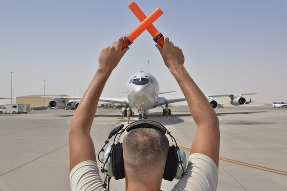 An Airman form the 7th Expeditionary Air Mobility Unit directs a Boeing E-8C Joint Surveillance Target Attack Radar Systems aircraft to park after completing its 100K combat hours milestone mission June 2, 2015 Al Udeid Air Base, Qatar. The E-8C JSTARS and its active duty, guard and reserve service members conduct missions overseas to support operations on the war on terror. During this time JSTARS completed 100K combat hours by continually flying 24/7 for 11.4 years. (U.S. Air Force photo/Staff Sgt. Alexandre Montes)