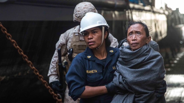 A U.S Navy Sailor assists a distressed mariner to medical staff aboard the USS Rushmore (LSD 47) at sea in the Makassar Strait, June 10, 2015. Rushmore rendered assistance to the distressed mariners in the waters between the Indonesian islands of Kalimantan and Sulawesi. Once on board, evacuees were provided food and medical attention by Marines and sailors of the 15th Marine Expeditionary Unit and Essex Amphibious Ready Group.