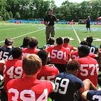 Staff Sgt. Travis McGlew gives a talk about physical and mental endurance to high school football players during the Semper Fidelis All-American Camp at St. John Preparatory High School in Danvers, Massachusetts, June 7. Nearly 200 top football players from high schools throughout the New England states, including New York, Pennsylvania and New Jersey, received training from the NFL and college football coaches while fighting for a spot to play in the 2016 Semper Fidelis All-American Bowl game in California. McGlew is a canvassing recruiter with Recruiting Substation Lawrence, Mass., Recruiting Station Portsmouth, New Hampshire.