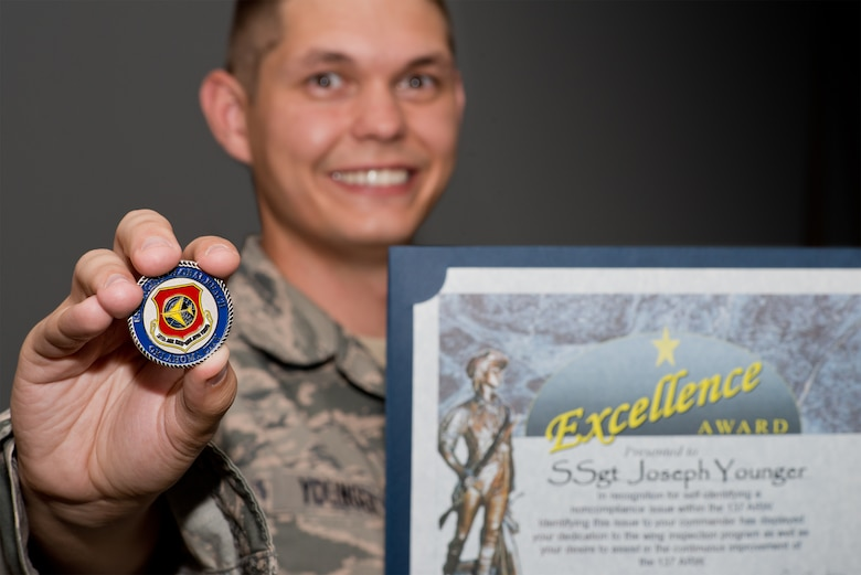 Staff Sgt. Joseph Younger, a member of the 137th Logistics Readiness Squadron, holds his Excellence Award, which he received after he reported an operations security issue, June 3, 2015.
