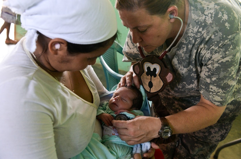 Lt. Col. Karen Rutherford, a Joint Task Force – Bravo Medical Element physician, performs a wellness check on a 13-day-old infant during a medical readiness training exercise June 2, 2015, at Corinto, Cortes, Honduras. The MEDRETE provided basic care and medication to more than 600 civilians of all ages. (U.S. Air Force photo by Staff Sgt. Jessica Condit)