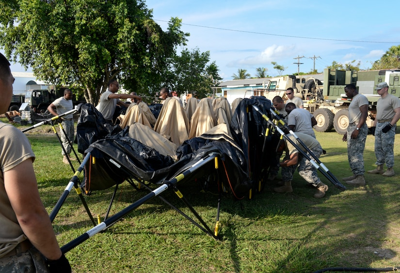 Members of the Joint Task Force-Bravo Army Forces Battalion set up temporary shelters for medical readiness exercise participants June 1, 2015, at Puerto Cortes Naval Station, Honduras. The ARFOR Battalion provided temporary shelters, supplies, communication support and many other amenities to the MEDRETE, supporting more than 100 participants. (U.S. Air Force photo by Staff Sgt. Jessica Condit)
