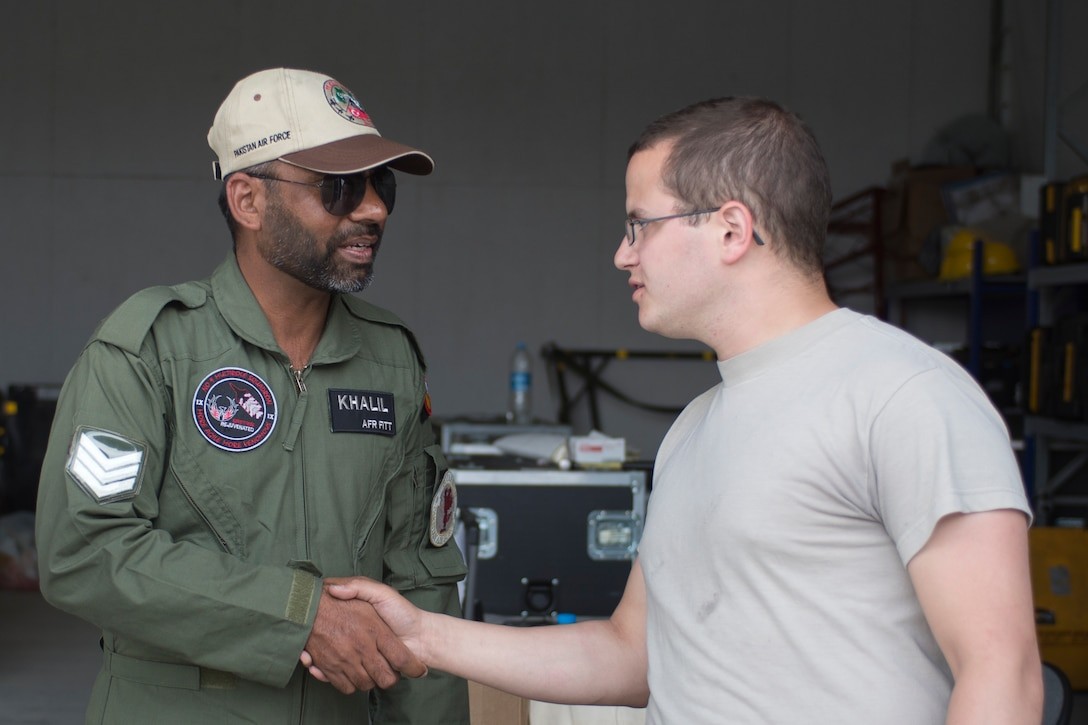 U.S. Air Force Senior Airman Alex Ross, 748th Aircraft Maintenance Squadron, right, shakes hands with a crew chief from the Pakistan Air Force during Anatolian Eagle 15 at 3rd Main Jet Base, Turkey, June 10, 2015. Anatolian Eagle is a two-week flying training exercise involving U.S. Air Forces in Europe units and multiple NATO partners. (U.S. Air Force photo by Tech. Sgt. Eric Burks/Released)