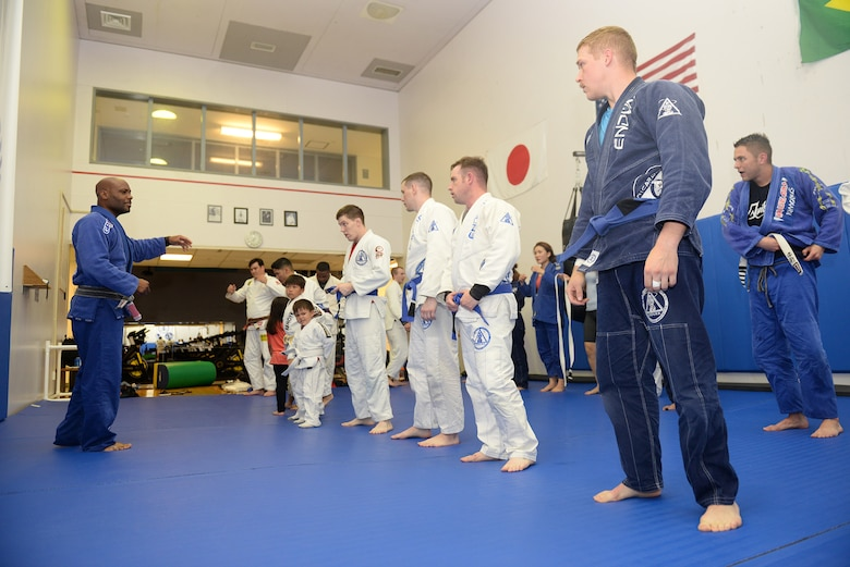 Master Sgt. Bob Williams, instructor of Endure, a jiu-jitsu class, gathers his students to recognize the accomplishments of two of the students at Yokota Air Base, Japan, June 10, 2015. Students received stripes on their belts to annotate advancement in skill level. (U.S. Air Force photos by Airman 1st Class Elizabeth Baker/Released)