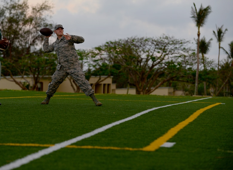 Senior Airman Presley Griffith, 36th Mobility Response Squadron executive assistant, passes a football June 6, 2015, at Andersen Air Force Base, Guam. Griffith created a free spring practice camp as volunteer coach and is working to become a history teacher and high school football coach. (U.S. Air Force photo by Senior Airman Alexander W. Riedel/Released)