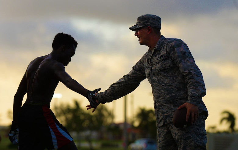 Senior Airman Presley Griffith, 36th Mobility Response Squadron executive assistant, right, compliments a high school athlete on a practice drill June 6, 2015, at Andersen Air Force Base, Guam. Griffith is a volunteer football coach and offers a free football spring practice camp three times per week as volunteer coach as a pre-season training opportunity to Andersen AFB student athletes. (U.S. Air Force photo by Senior Airman Alexander W. Riedel/Released)