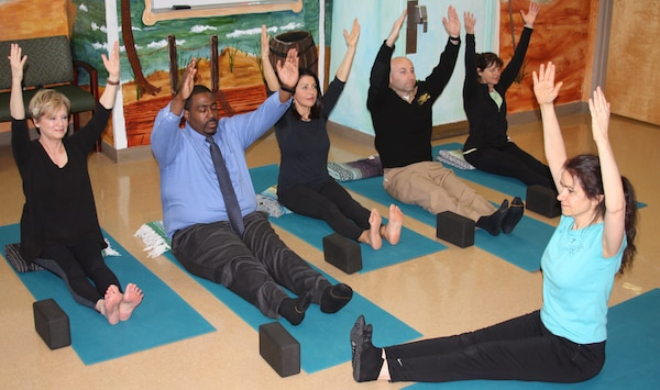 """Yoga is one of several mind-body skills now offered at Walter Reed National Military Medical Center's 7-West inpatient psychiatry ward and in the four-week, psychiatric outpatient Continuity Service """"day program."""" Staff members recently participated in one of the classes. Photo by Katrina Skinner"""