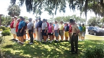 "Sgt. Jonathan Owens, senior drill instructor assigned to Recruit Processing Company, Support Battalion, greets golfers before a tournament at the Legends at Parris Island golf course June 8, 2015. The ""receiving"" tournament was the first of four scheduled tournaments leading up to the celebration of Parris Island's centennial anniversary in October."