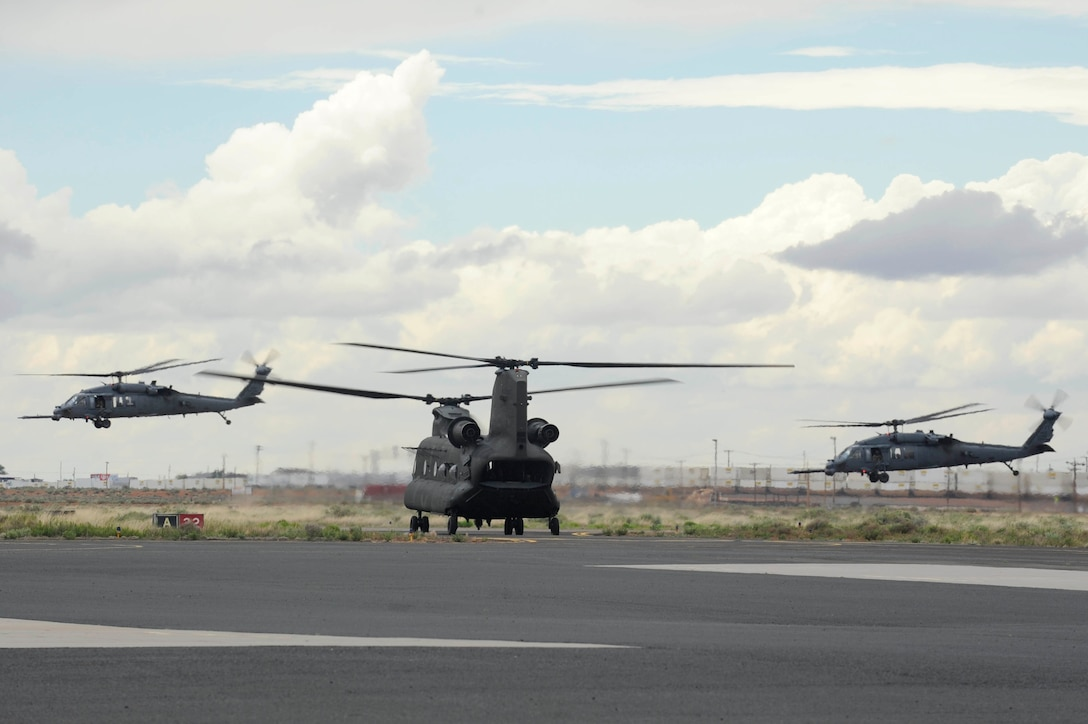 Two HH-60G Pave Hawks take off as a CH-47 taxis during an Angel Thunder 2015 mass casualty exercise at Winslow–Lindbergh Regional Airport, Ariz., June 5, 2015. U.S. military forces and partner nations worked together during the exercise to transport simulated patients from Camp Navajo Training Site to the casualty collection point located at the Winslow–Lindbergh Regional Airport. (U.S. Air Force photo/Tech. Sgt. Courtney Richardson)