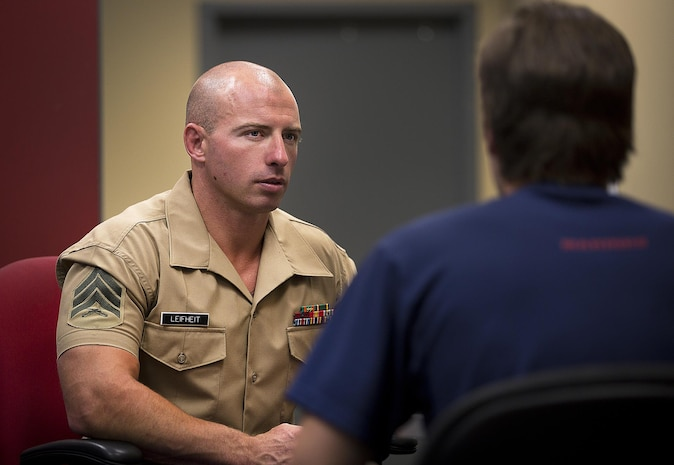 Sgt. Cody Leifheit, a Marine recruiter in Lewiston, Idaho, answers questions about the Marine Corps from enlistee Brandon Roberts at his recruiting office June 10, 2015. Leifheit, a 28-year-old infantry Marine from Ferndale, Washington, responded to a 19-year-old man hanging himself from a tree outside his house June 7. Without hesitation, Leifheit climbed up the tree 25 feet and took hold of the man, who wasn't breathing and lacked a pulse. Leifheit worked to keep him alive until first responders arrived, continuously performing chest compressions as the man faded in and out. Despite spending 48 hours in a coma, the man survived. (U.S. Marine Corps photo by Sgt. Reece Lodder)