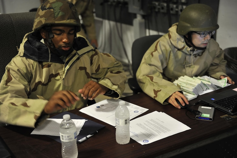 Senior Airman Jonathan Chapman and Staff Sgt. Joshua Reber, assigned to the 1st Special Operations Comptroller Squadron, count 'cash' and review the end of day cash accountability during the Financial Management Warrior expeditionary exercise on Hurlburt Field, Fla., June 6, 2015. The training is based on 'Top Dollar,' a finance exercise from the 1990's, and is anticipated to become an annual or semi-annual training event for Eglin and Hurlburt Airmen. (U.S. Air Force photo/Amn Kai White)