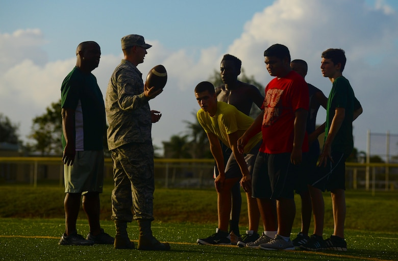Jacob Dowdell, the Guam High School head coach, left, supervises Senior Airman Presley Griffith, a 36th Mobility Response Squadron executive assistant, second from left, as he teaches a free football spring practice camp June 8, 2015, at Andersen Air Force Base, Guam. Griffith hopes to someday become a high school football coach and volunteers his time to offer an additional preseason training opportunity to local high school athletes. (U.S. Air Force photo/Senior Airman Alexander W. Riedel)