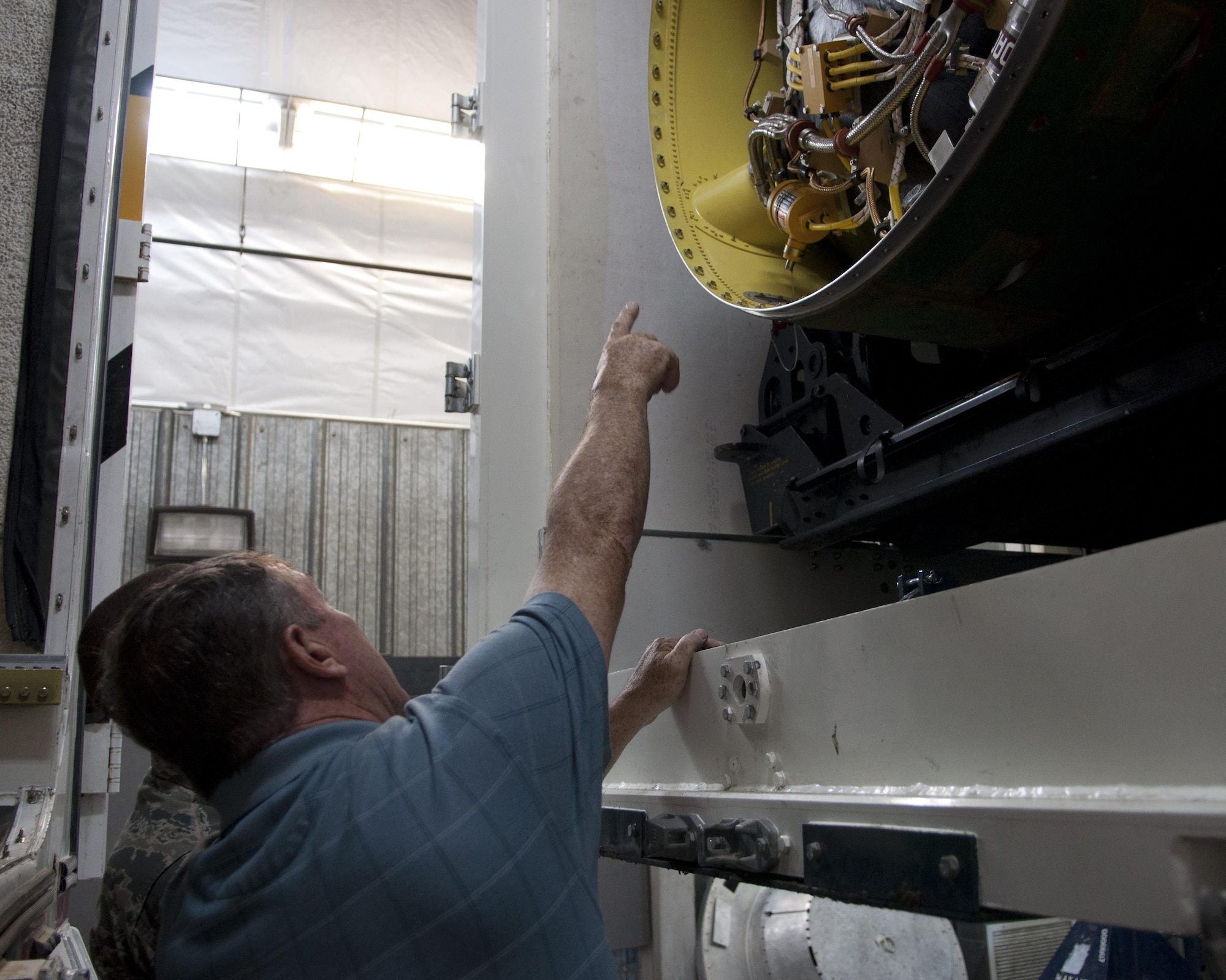 Richard Mullee, the 90th Missile Wing Safety Office missile safety superintendent, examines the midsection of the booster of the Minuteman III ICBM during the 90th Missile Maintenance Squadron's annual weapons safety inspection June 9, 2015, on F.E. Warren Air Force Base, Wyo. Inspections play a vital part in the mission of the weapon safety office. They provide the office the opportunity to see the mission and work environment firsthand, in order to catch any issues before they worsen. (U.S. Air Force photo/Airman 1st Class Malcolm Mayfield)