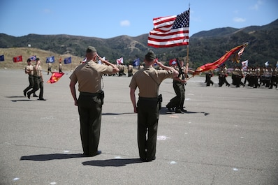 Lieutenant Col. Lance A. Jackola, previous battalion commander of 1st Battalion, 1st Marine Regiment, 1st Marine Division, and his successor Lt. Col. Steven M. Sutey, watch as the Marines and Sailors of 1st Battalion pass in review at the end of the change of command ceremony. Sutey has several past deployments with the 1st Marine Division and said he is proud to command and serve once again with the unit. (U.S. Marine Corps photo by Cpl. Carson A. Gramley/Released)