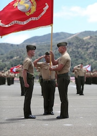 Lieutenant Col. Lance A. Jackola, battalion commander of 1st Battalion, 1st Marine Regiment, 1st Marine Division, formally relinquishes his command by handing the battalion colors to his successor Lt. Col. Steven M. Sutey. Sutey has several past deployments with the 1st Marine Division and said he is proud to command and serve once again with the unit. (U.S. Marine Corps photo by Cpl. Carson A. Gramley/Released)