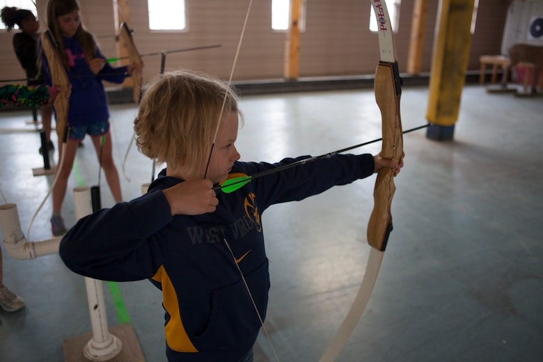 Trinity Facemire, 7, daughter of Chief Master Sgt. John Facemire, 90th Mission Support Group superintendent, prepares to shoot her bow in the archery range on F.E. Warren Air Force Base, Wyo., June 11, 2015. The archery range was one of the activities Outdoor Recreation hosted as part of Basic Recreation Adventure Training Camp for children aged 7-10.  (U.S. Air Force photo by Lan Kim)