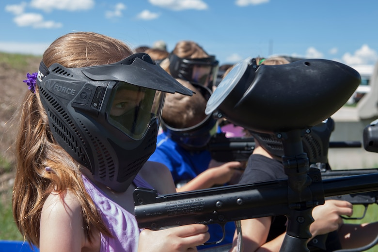 Samara Wright, 8, daughter of Master Sgt. Steven Wright, 20th Air Force enlisted aide, shoots paintballs at the paintball field obstacle course on F.E. Warren Air Force Base, Wyo., June 9, 2015. Shooting the paintballs was one of the activities Outdoor Recreation hosted as part of Basic Recreation Adventure Training Camp for children aged 7-10. (U.S. Air Force photo by Lan Kim)