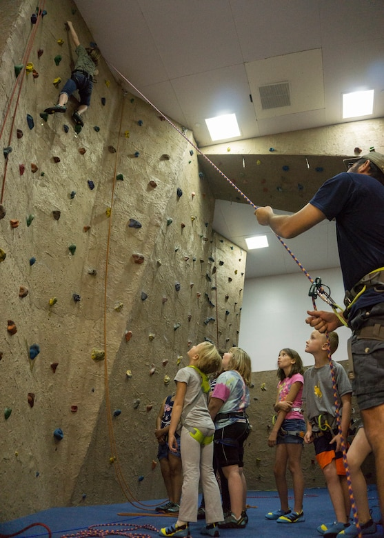 Baileigh Mitchell, 9, daughter of Master Sgt. Kenneth Mitchell, 90th Missile Security Forces Squadron, climbs the indoor rock wall in the Fall Hall Community Center on F.E. Warren Air Force Base, June 8, 2015. The rock wall was one of the activities Outdoor Recreation hosted as part of Basic Recreation Adventure Training Camp for children aged 7-10. (U.S. Air Force photo by Lan Kim)