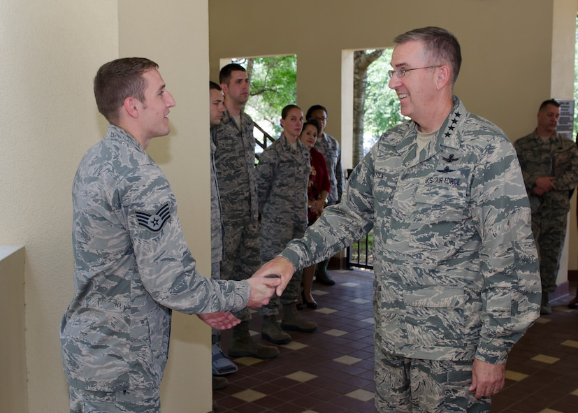 Gen. John E. Hyten, Air Force Space Command commander presents a commander's coin to Staff Sgt. Jacob W. Stowe, a Cyber Operations Analyst assigned to the 68th Network Warfare Squadron during his visit to Joint Base San Antonio - Lackland, Texas, June 2. Stowe was one of serveral cyber warriors within 24th Air Force who were recognized by Hyten for standing out as top performers. (U.S. Air Force photo by Master Sgt. Luke P. Thelen/Released)