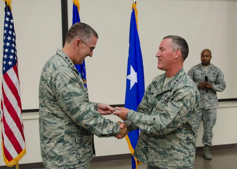 "Gen. John E. Hyten, Air Force Space Command commander accepts a ""Ranger's"" badge; 24th Air Force's mascot from Maj. Gen. B. Edwin Wilson, 24th Air Force commander during his visit to Joint Base San Antonio - Lackland, Texas, June 3. Wilson presented Hyten the badge as a token of appreciation for sharing his time and insights with the men and women of 24th Air Force. (U.S. Air Force photo by Master Sgt. Luke P. Thelen/Released)"