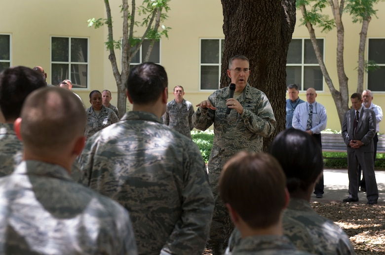 Gen. John E. Hyten, Air Force Space Command commander speaks in a courtyard while surrounded by the men and women of the 67th Cyberspace Wing during his visit to Joint Base San Antonio - Lackland, Texas, June 2. Hyten took the time to answer questions from several personnel, to share his priorities and vision and to personally recognize multiple cyber professionals for being outstanding performers. (U.S. Air Force photo by Master Sgt. Luke P. Thelen/Released)