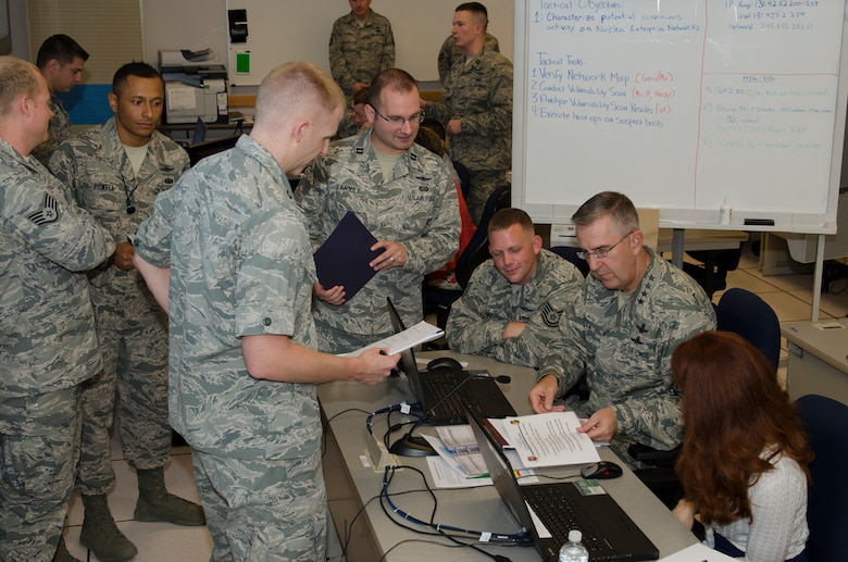 Gen. John E. Hyten, Air Force Space Command commander receives a simulated intelligence report from Capt. William Garvey, an intelligence analyst assigned to the 318th Operations Support Squadron, while participating in a simulated cyber mission during his visit to Joint Base San Antonio - Lackland, Texas, June 2. During the simulation, Hyten was given a scenario-based, hands-on experience which demonstrated an example of the continuation training provided to Air Force cyber operators assigned to Cyber Protection Teams. (U.S. Air Force photo by Master Sgt. Luke P. Thelen/Released)