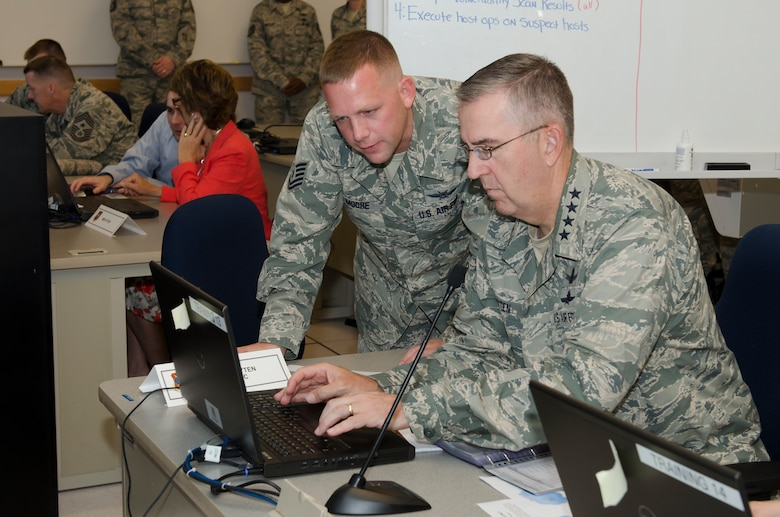 "Gen. John E. Hyten (right), Air Force Space Command commander receives instructional support from Technical Sgt. Bryan Moore a Cyber Vulnerability Assessment/Hunter (CVA/H) weapon system operator with the 92d Information Operations Squadron while participating in a scenario-based cyber training mission known as ""CyberDome"" during a visit to Joint Base San Antonio - Lackland, Texas, June 2. During the simulation, Hyten was tasked with investigating a training network for indicators of compromise and was tested on his ability to properly identify malicious activity. (U.S. Air Force photo by Master Sgt. Luke P. Thelen/Released)"