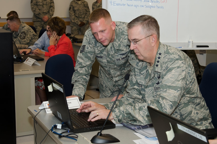 """Gen. John E. Hyten (right), Air Force Space Command commander receives instructional support from Technical Sgt. Bryan Moore a Cyber Vulnerability Assessment/Hunter (CVA/H) weapon system operator with the 92d Information Operations Squadron while participating in a scenario-based cyber training mission known as """"CyberDome"""" during a visit to Joint Base San Antonio - Lackland, Texas, June 2. During the simulation, Hyten was tasked with investigating a training network for indicators of compromise and was tested on his ability to properly identify malicious activity. (U.S. Air Force photo by Master Sgt. Luke P. Thelen/Released)"""
